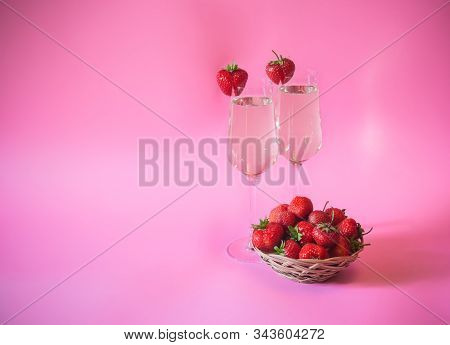 Two Glasses Of Champagne And Fresh Strawberry In Wicker Basket On Pink Background. View With Copy Sp