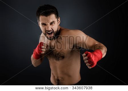 Sportsman Boxer Throwing A Fierce And Powerful Punch. Muscular Man With Red Bandage On Hands On Blac