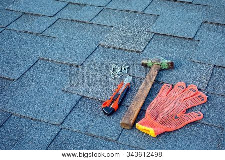Close Up View On Asphalt Shingles On A Roof  With Hammer,nails And Stationery Knife.