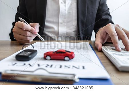 Car Rental And Insurance Concept, Young Salesman Receiving Money And Giving Car's Key To Customer Af