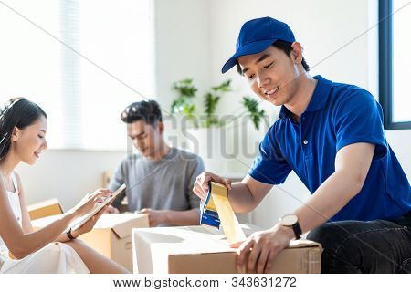 House Moving And Packing Service. Asian Man In Blue Shirt Uniform Using Tape To Package Box At Custo