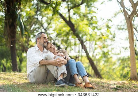 Senior Elder Caucasian Couple Sitting On Ground Together In Park In Autumn. Wife Resting Head On Hus