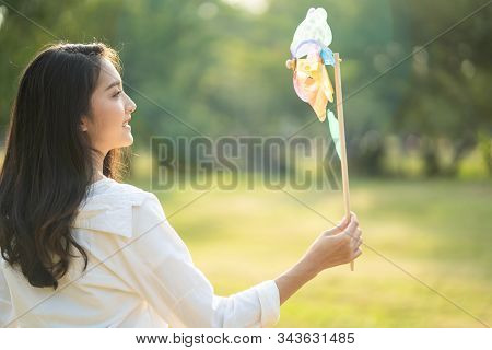Young Cute, Beautiful Asian Woman Holding Windmill Toy With One Hand In Green Park In The Evening. G