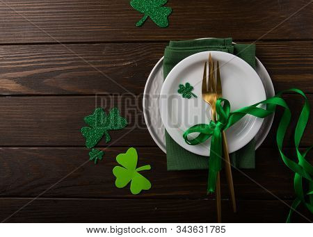 St. Patrick's Day Green Shamrocks With Fork, Spoon, And Napkin On Rustic Brown Wood Board Background