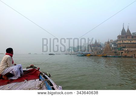 Varanasi, India, November, 2019: Indian Man Sitting On The Tip Of A Wooden Boat, Overlooking The His