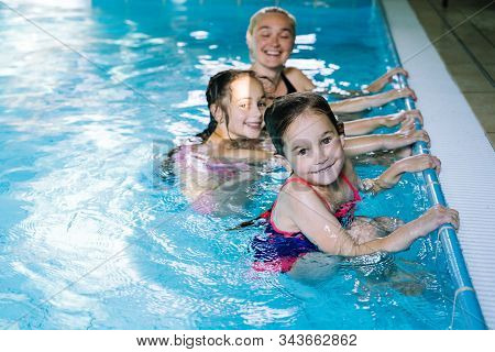 Mother With Two Daughters Having Fun In Indoor Swimming-pool.