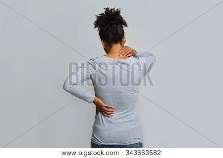African Woman With Neck And Back Pain, Rubbing Her Painful Body Over Grey Background, Back View