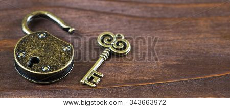 Escape game room concept, vintage golden key and opened padlock, web banner with copy space