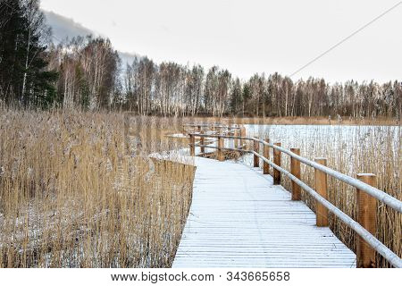 Wooden Bridge Trail Along The Shoreline Of The Lake Covered Of The First Snow.