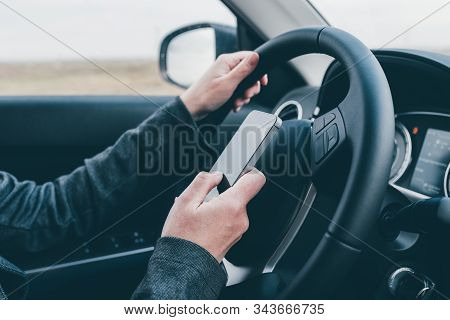 Texting And Driving Is Dangerous Behavior In Traffic, Close Up Of Female Hand Typing Text Message On