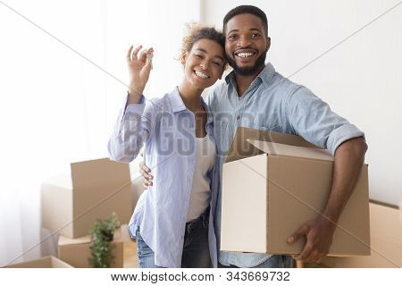 Joyful Afro Spouses Showing Key Embracing And Holding Moving Box After Relocation Standing In New Fl