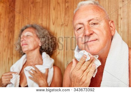 Senior couple sweats in the spa sauna or steam room at the spa hotel