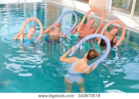 Group of seniors in the swimming pool in rehab doing water aerobics