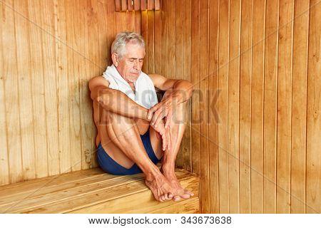 Senior man sweats in the sauna or steam sauna in the spa hotel