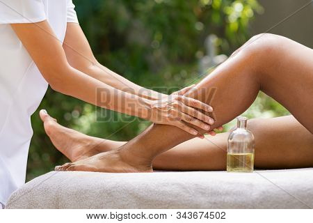 Closeup of masseuse hands giving essential oil massage to woman in outdoor spa resort. African american girl getting cellulite treatment. Young woman getting feet massage treatment at spa.