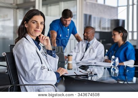 Portrait of mature female doctor sitting in meeting room with specialist and nurses discussing case in background. Successful woman doctor looking at camera with medical staff brainstorming.