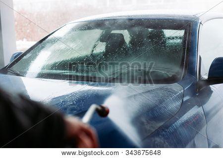 Man Washing His Car In Car Wash Self Service Shop. Car Maintenance Concept