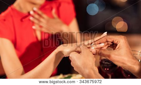 Wedding Proposal. Unrecognizable Man Putting On Engagement Ring On Girfriends Hand Asking To Marry H