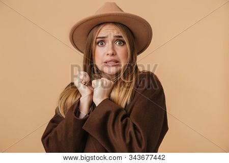 Image of young scared girl wearing hat and coat pressing her arms and expressing fright isolated over beige background