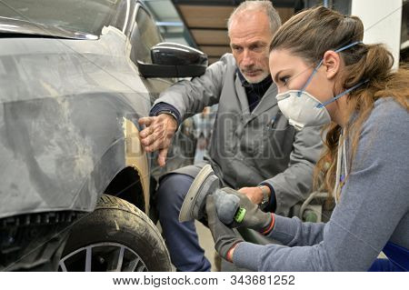 Apprentice with instructor working on vehicle
