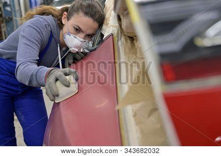 Apprentice working on car body shell in workshop