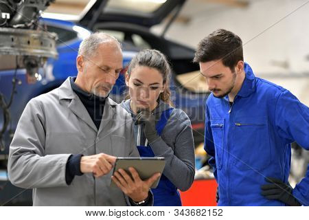Apprentice with instructor using tablet in workshop