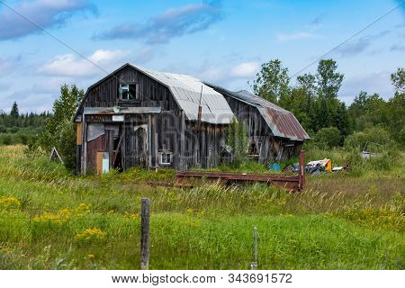 A Wide Angle View Of A Dilapidated Farm Building. Neglected Wood Barn In A State Of Disrepair Surrou