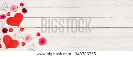 Valentines Day Banner With Corner Border Of Hearts, Flowers And Decor Against A Rustic White Wood Ba