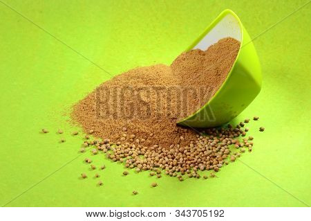Coriander Seeds And Powdered Coriander In Green Container On Green Background
