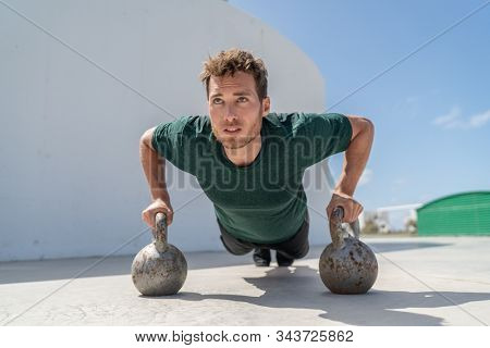 Training fit man exercising pushup exercises on kettlebell weights in gym. Fitness athlete strength training body core doing push-ups holding on kettlebells bodyweight floor exercises at outdoor gym.