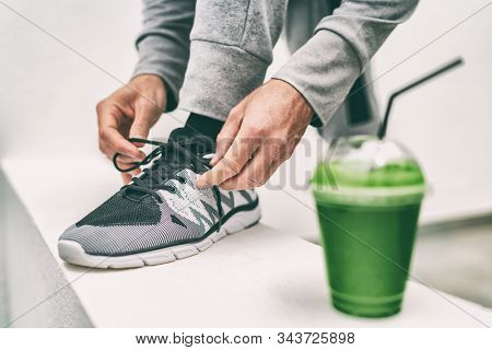 Green juice exercise man getting ready for cardio run workout tying running shoes laces drinking smoothie drink. Fitness runner athlete lacing shoe, with vegetable detox cleanse juice healthy eating.