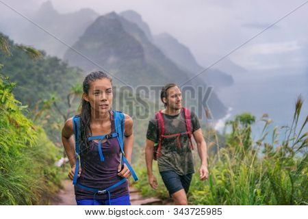 Hiking hikers woman and man trekking on trail trek with backpacks living healthy active lifestyle. Hiker girl walking on hike in mountain nature landscape wet scenery, Na Pali Coast, Kauai, Hawaii.