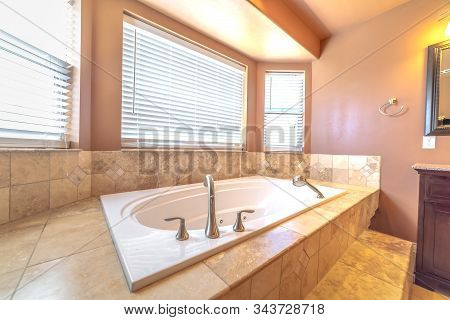 Elevated Built In Bathtub Against The Bay Windows With Blinds Of A Bathroom