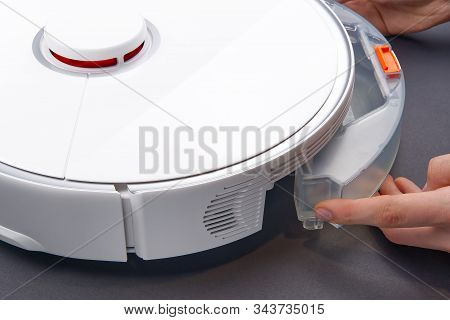 Robot Vacuum Cleaner Replacing A Container With Water. Robot Vacuum Cleaner Isolated On Gray Backgro