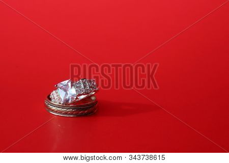 Man and Woman's Wedding Rings. Engagement Ring. Wedding Ring. Gold and Diamond Engagement or Wedding Ring. Isolated on Red. Room for text. clipping path. Wedding Rings are enjoyed world wide.