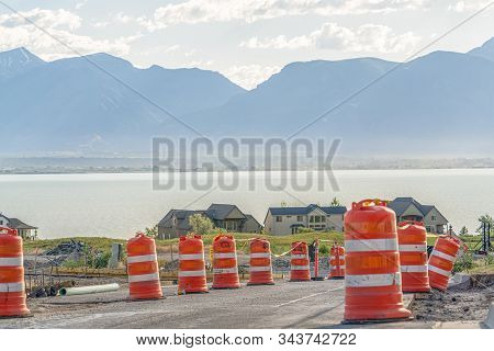 Road Under Construction With Blurry View Of Homes Lake And Mountain Against Sky