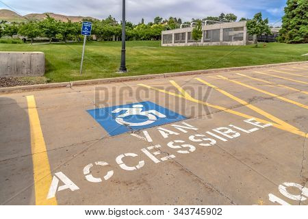 Handicapped Parking Lot With Painted Handicap Symbol And Van Accessible Sign