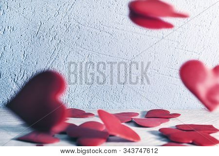 Red Hearts Fall From Top To Bottom On A Wooden Table Against A Background Of Stucco Covered Wall. Al