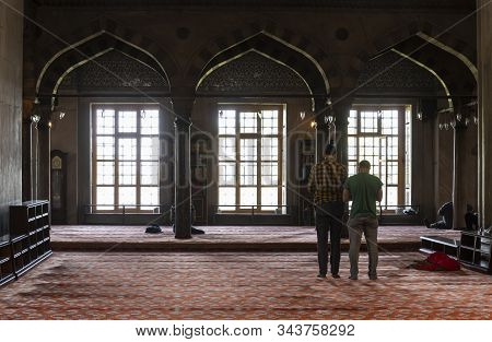 Istanbul, Turkey - April 29, 2019: People, Two Men, Praying In The Colorful, Old, Famous Islamic Blu