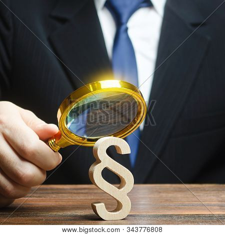 A Man Examines A Paragraph Figure With A Magnifying Glass. Judicial Practice. Legitimacy. Studying L