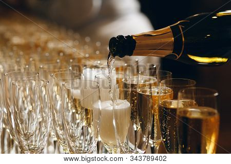 Bartender Pouring Champagne Or Wine Into Wine Glasses On The Table At The Outdoors Solemn Wedding Ce