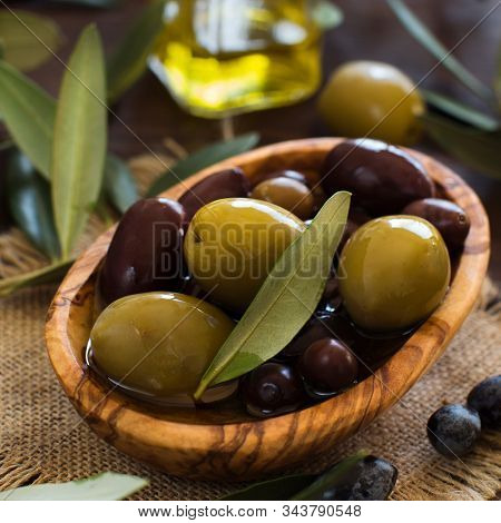 Olive Oil And Olives On Wood Background