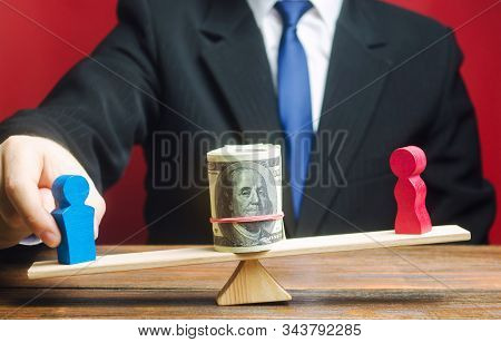 The Businessman Puts The Figure Of A Man And A Woman On The Scales With Money. Concept Of Gender Pay