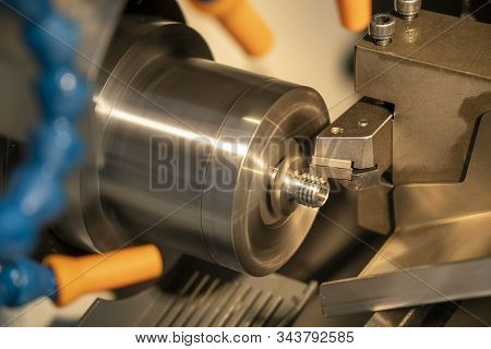 The Cnc Lathe Machine In Metal Working Process Cutting The Screw  Parts With The Cutting Tools. The