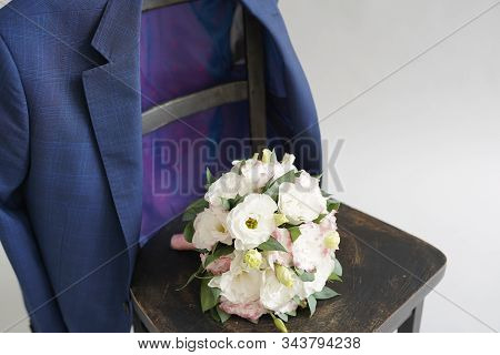 The Bride's Bouquet On The Chair With Groom's Blue Jaket