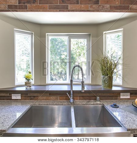 Square Kitchen Sink Close Up With Bay Windows In The Background