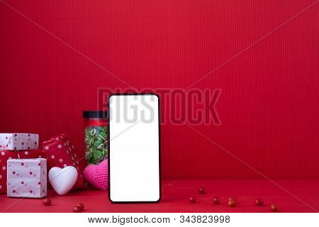 Copy Space On Red Valentines Background With Blank Screen On Smart Phone And Valentines Day Gift.
