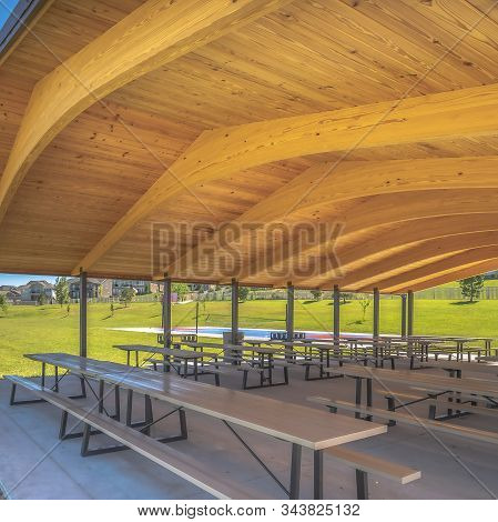 Square Frame Park Pavilion With White Tables And Seats Under The Brown Wooden Ceiling