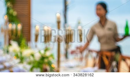 Blurred Of Table In The Restaurant Witch Candles And Servant On The Beach, Bali