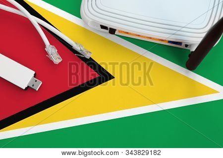 Guyana Flag Depicted On Table With Internet Rj45 Cable, Wireless Usb Wifi Adapter And Router. Intern